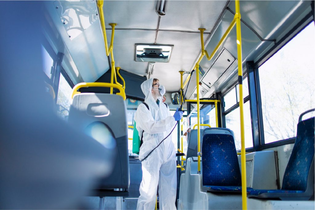 young man in transportation setting applies AEGIS antimicrobial surface treatment by spray to bus interior